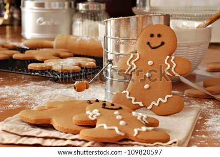 Smiling gingerbread man standing next to flour sifter with baking ingredients and additional gingerbread cookies in background.  Partially decorated cookies in foreground.  Closeup with shallow dof.