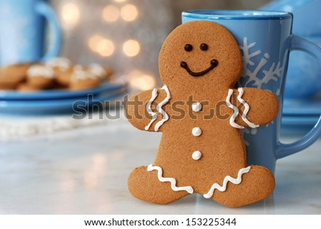 Smiling gingerbread man standing next to snowflake mug.  Plate of additional cookies and defocused holiday lights in background.  Closeup with shallow dof.  Copy space included for text. - stock photo