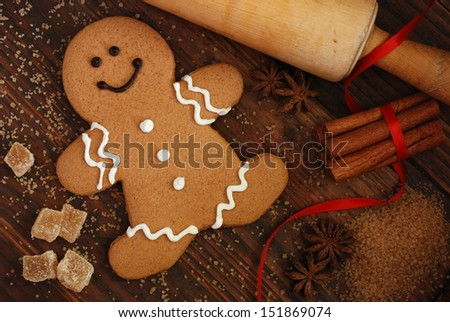 Smiling gingerbread man with sugar, spices, and vintage rolling pin on rustic, dark wood background.  Low key still life with directional, natural lighting for effect. - stock photo