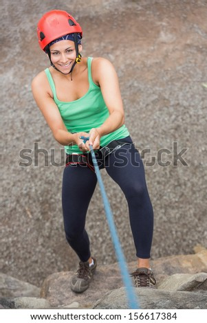 Smiling girl abseiling down rock face looking up at camera - stock photo