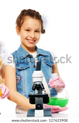 Smiling girl and chemistry - microscope and lab glass flasks - stock photo