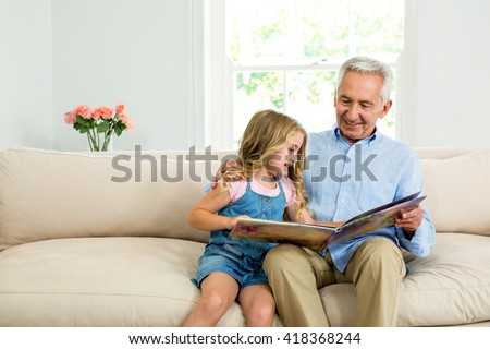 Smiling girl and granddad with picture book while sitting on sofa