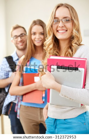 Smiling girl and her groupmates on background looking at camera