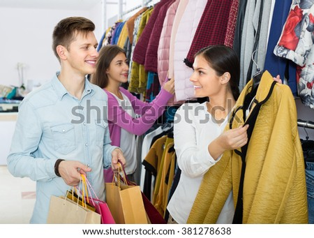 Smiling girl and her young boyfriend doing many purchases at the clothing shop  - stock photo