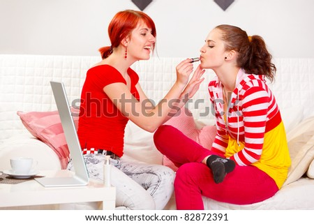 Smiling girl applying lipstick to her girlfriend  at living room - stock photo