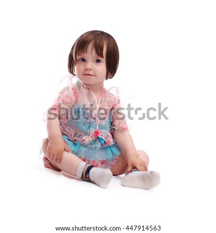 smiling girl baby in a colorful dress isolated on white background