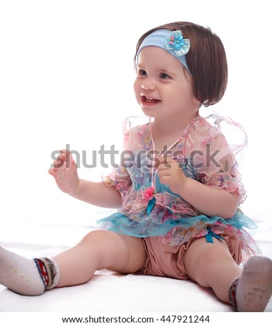 smiling girl baby in a colorful dress isolated on white background  - stock photo