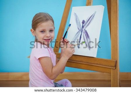 Smiling girl beside her picture on an easel - stock photo
