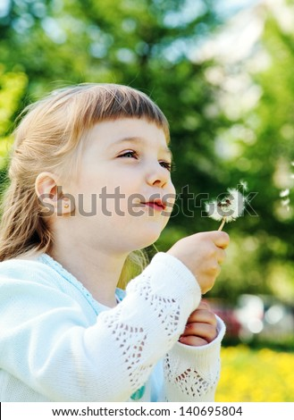 Smiling girl blowing dandelion in park at sunny day