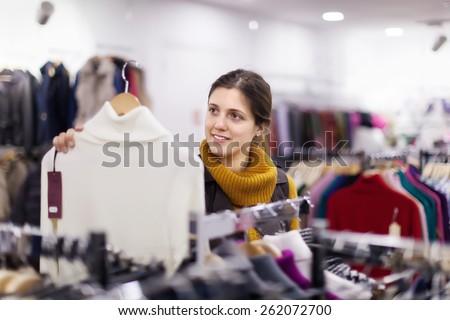 Smiling girl choosing  sweater at clothing shop - stock photo