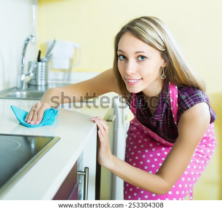 Smiling girl cleaning furniture in kitchen - stock photo