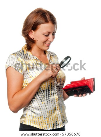 Smiling girl considers a purse through a magnifier - stock photo