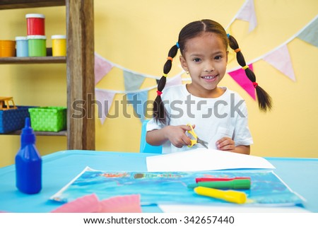 Smiling girl cut up some paper at the desk