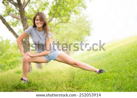 Smiling girl doing exercises in park - stock photo