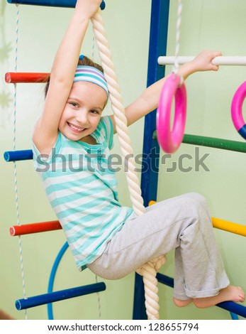 smiling girl doing sports gymnastics at home gym - stock photo