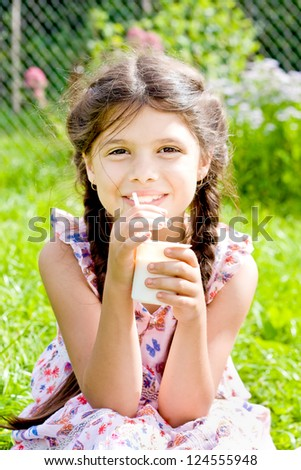 Smiling girl eats yogurt