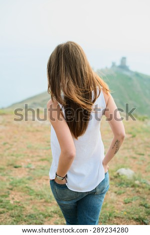 Smiling girl enjoys fine warm spring weather highly in mountains against the sea. Beautiful modern woman with long hair in a white shirt and blue jeans outdoors - stock photo