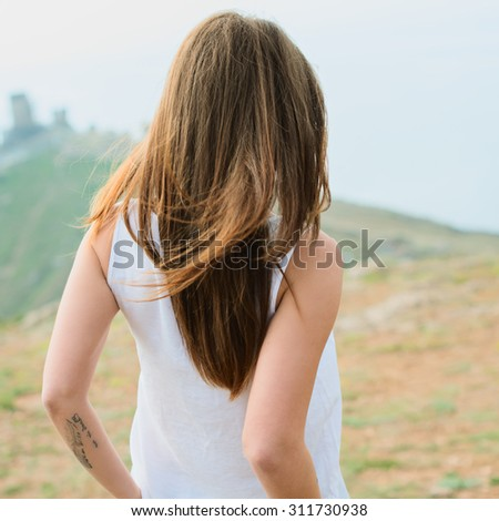 Smiling girl enjoys fine warm spring weather highly in mountains against the sea. Beautiful modern woman with long hair in a white shirt and blue jeans outdoors. Photo with instagram style filters - stock photo