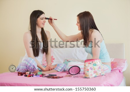 Smiling girl giving her friend a makeover at sleepover in bedroom at home - stock photo