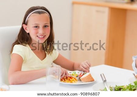 Smiling girl having dinner at the dinner table - stock photo
