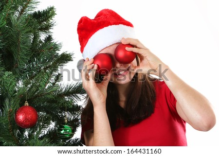 Smiling girl having fun hiding her eyes with red Christmas balls