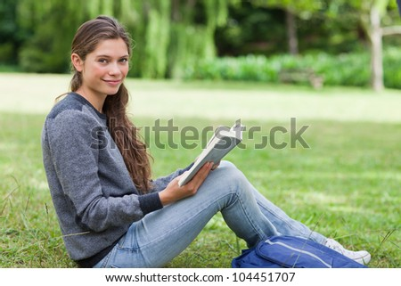 Smiling girl holding a book on her knees while sitting on the grass in the countryside