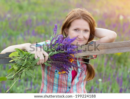 smiling girl holding a bouquet at the fields  - stock photo