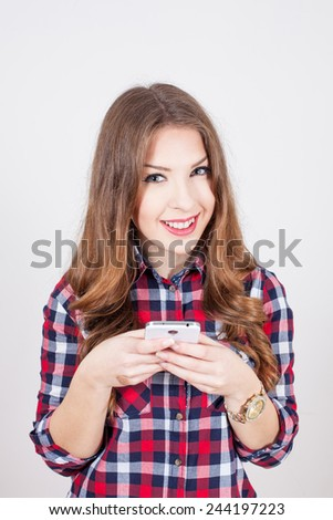 smiling girl holding a phone and typing a message