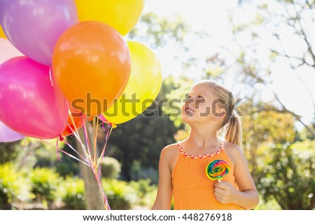 Smiling girl holding balloons and lollypop in the park on a sunny day - stock photo