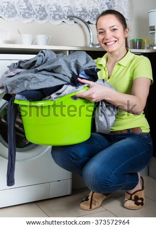 Smiling girl holding basin with laundry at kitchen