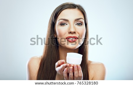 Smiling girl holding beauty skin care cream in glass jar. Isolated studio portrait.