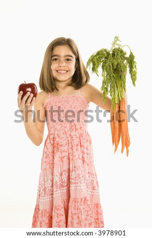 Smiling girl holding bunch of carrots and apple against background.