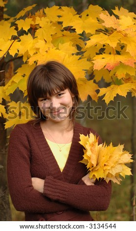 Smiling girl holding bunch of yellow maple leaves - stock photo