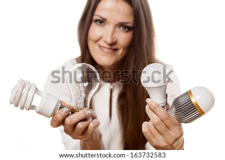 smiling girl holding LED bulbs in one and the old types of bulbs in the other hand