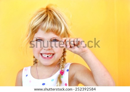 Smiling girl holding missing tooth - stock photo