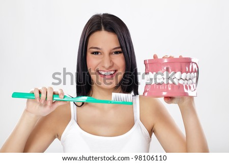 Smiling girl holding model of teeth and toothbrush - stock photo