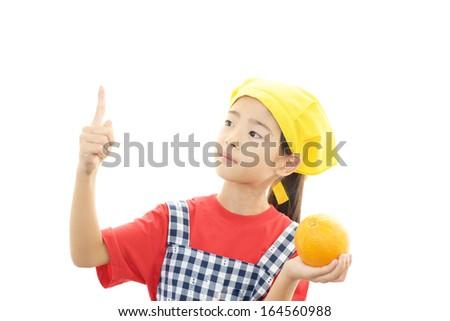 Smiling girl holding orange - stock photo