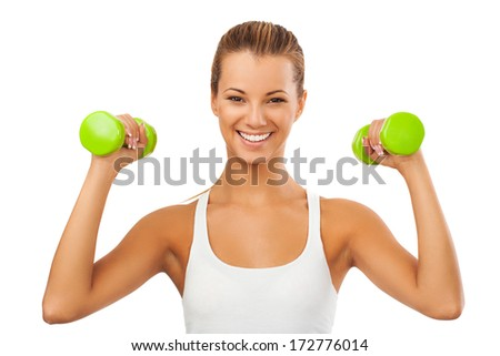 Smiling girl holding weights and showing muscles - stock photo