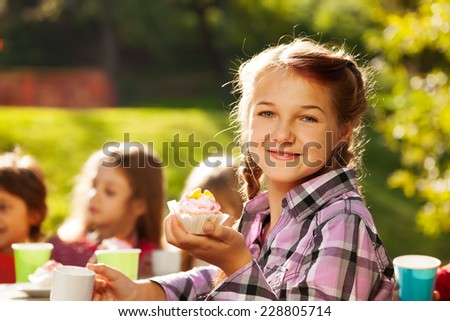 Smiling girl holds cupcake with her friends behind