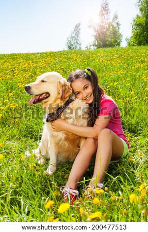 Smiling girl hugs cute dog sitting on the grass