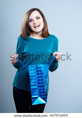 smiling girl in a blue t-shirt holding a shopping bag .On a gray background  - stock photo