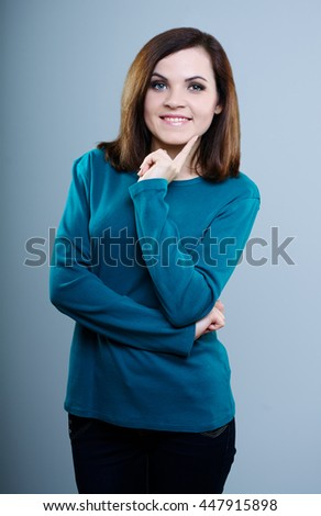 smiling girl in a blue t-shirt with your finger touches the face on a gray background - stock photo