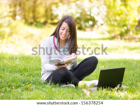 Smiling girl in a park with a book and laptop