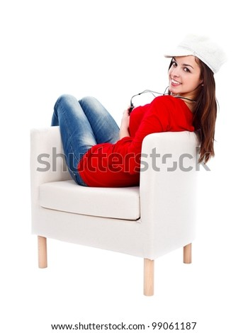 Smiling girl in armchair with mp3