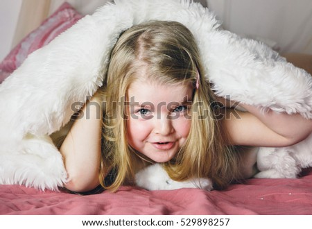 Smiling girl in bed under the blanket. Happy child girl having fun .Adorable little girl awaked up in bed