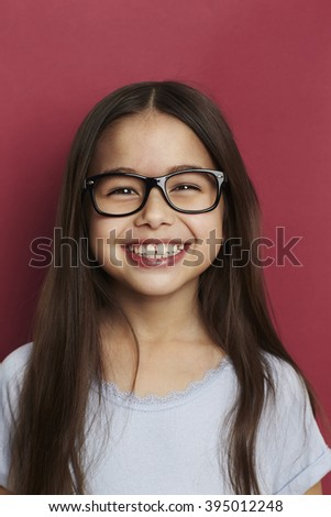 Smiling girl in front of red background, smiling