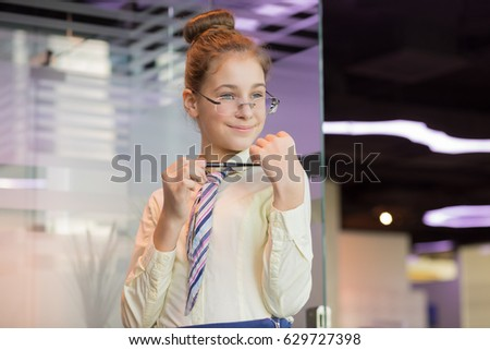 Smiling girl in glasses and tie poses with pen in modern office