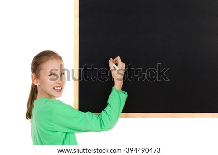 Smiling girl in green blouse holding white chalk writing on a blackboard and looking at camera. Waist up studio shot isolated on white.
