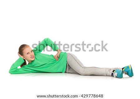 Smiling girl in green blouse, jeans and sneakers lying on a floor, holding hand on hip and looking at camera. Side view. Full length studio shot isolated on white. - stock photo