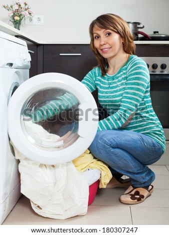 Smiling girl in green using washing machine at home